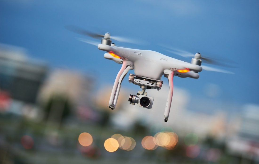 drone quadcopter with digital camera flying or hovering in evening blue sky over the city